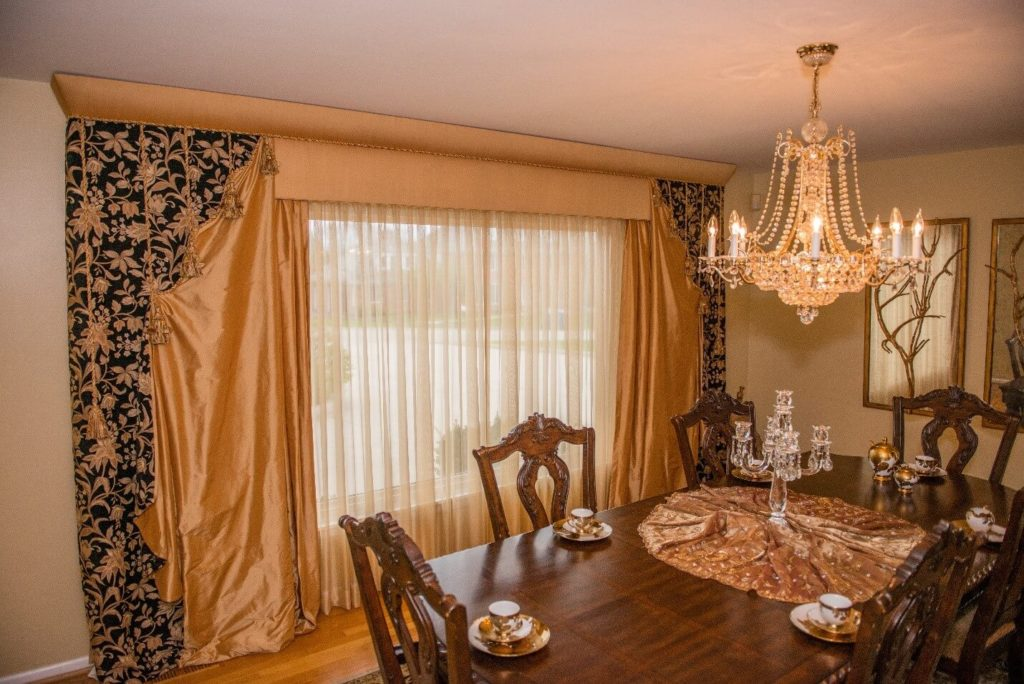 Luxurious custom draperies make this dining room special! An extraordinary cornice and tapestry drapery panels pulled with ropes and tassels are elements that add opulence and poise to this traditional dining room. (Burr Ridge IL)