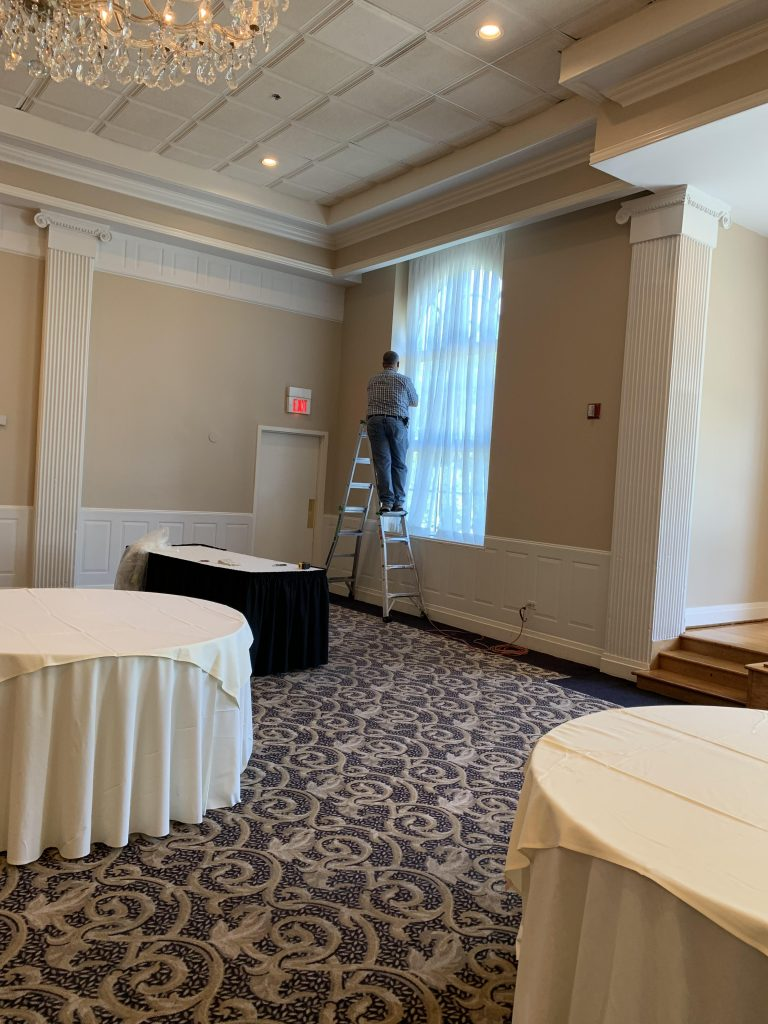 man installing drapes at event space